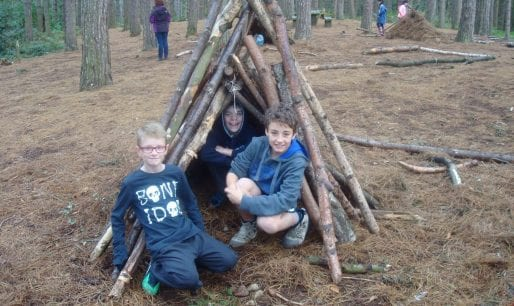Siblings building tree den in forest