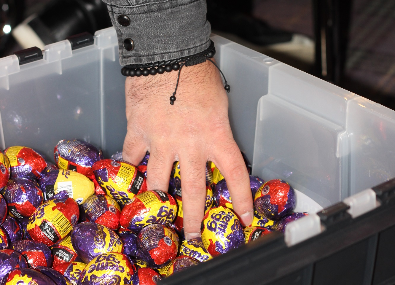 Hand grabs handful of creme eggs