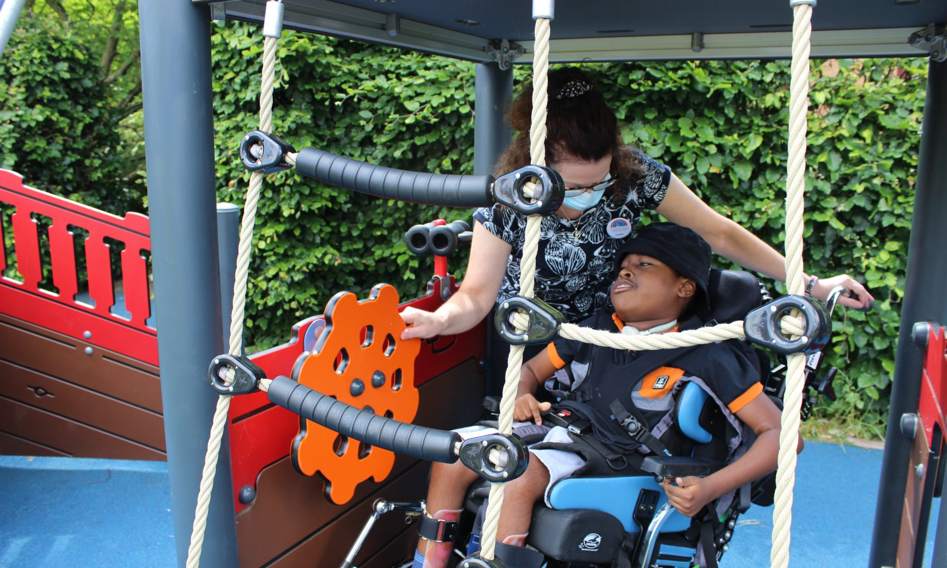 Child in wheelchair with nurse in garden pirate ship at Francis House